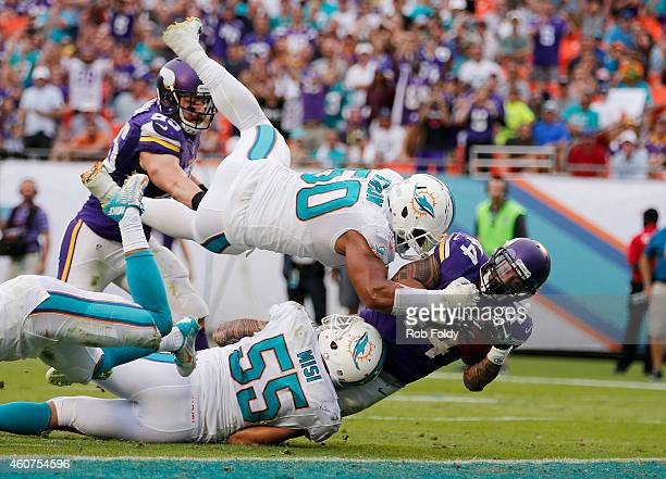 Running back Matt Asiata of the Minnesota Vikings scores a fourth quarter touchdown as defensive end Olivier Vernon of the Miami Dolphins goes...