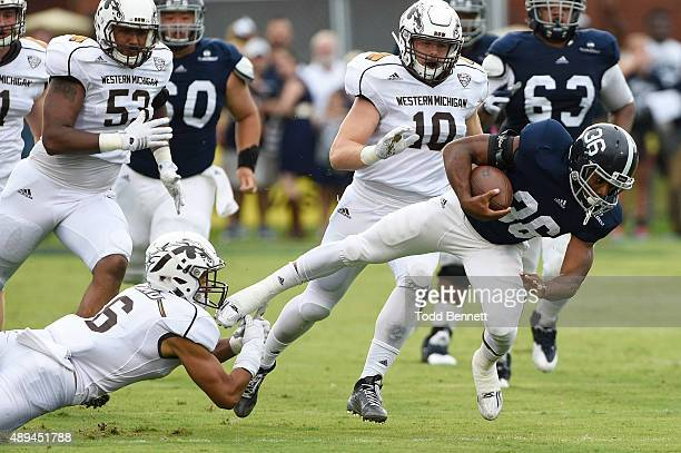 Running back Matt Brieda of the Georgia Southern Eagles is tripped up by safety Asantay Brown of the Western Michigan Broncos during the first...