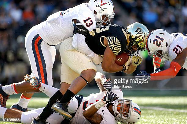 Running back Matt Colburn of the Wake Forest Demon Deacons is stopped by linebacker Chris Peace of the Virginia Cavaliers, safety Quin Blanding and...