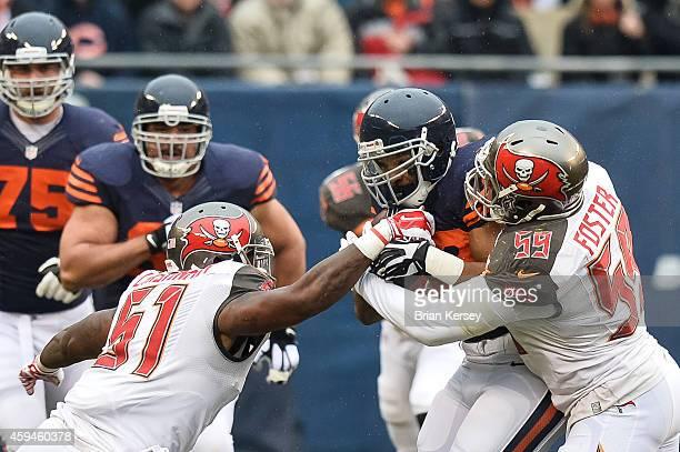 Running back Matt Forte of the Chicago Bears carries the ball against outside linebacker Danny Lansanah and middle linebacker Mason Foster of the...