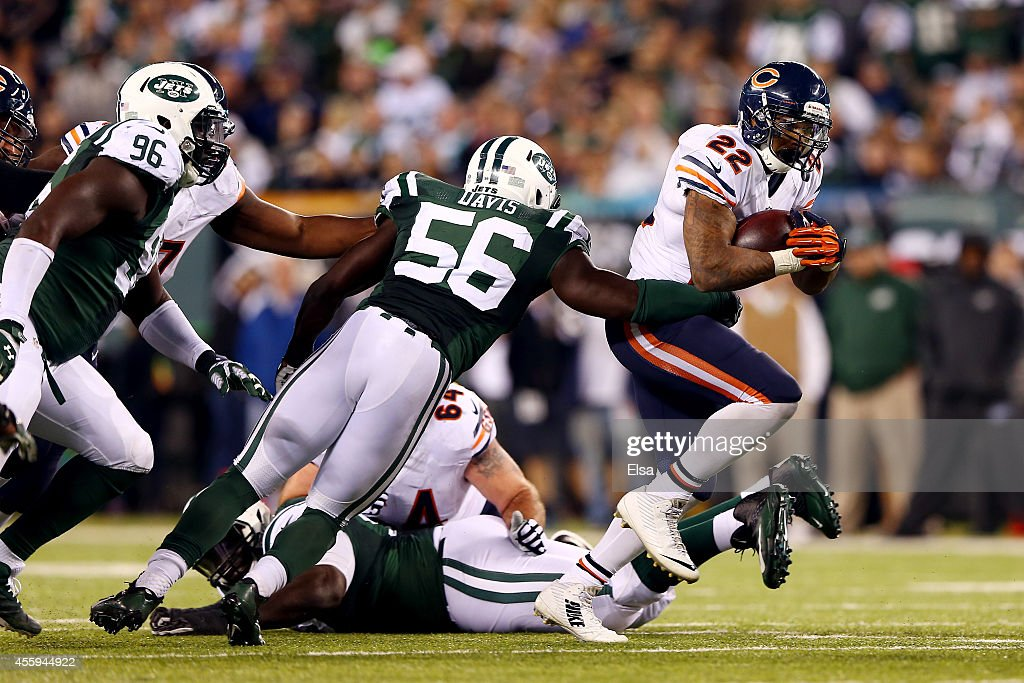 Running back Matt Forte #22 of the Chicago Bears carries the ball as inside linebacker Demario Davis #56 of the New York Jets tries to make the tackle during a game at MetLife Stadium on September 22, 2014 in East Rutherford, New Jersey.