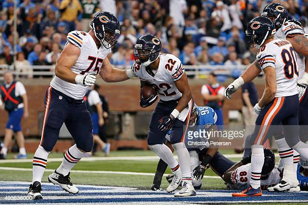 Running back Matt Forte of the Chicago Bears celebrates with offensive tackle Kyle Long after scoring a touchdown against the Detroit Lions during...