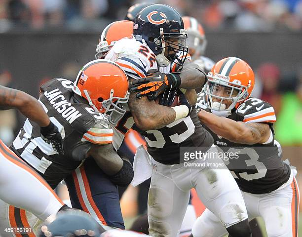 Running back Matt Forte of the Chicago Bears runs the football while being tackled by defensive back Joe Haden Tashaun Gipson and linebacker D'Qwell...
