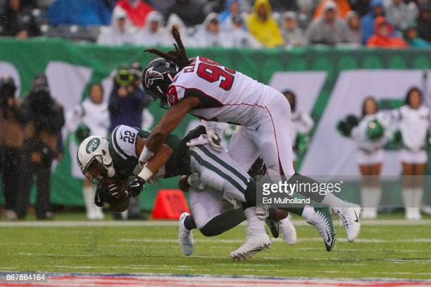 Running back Matt Forte of the New York Jets gets tackled by defensive end Adrian Clayborn of the Atlanta Falcons during the first half of the game...