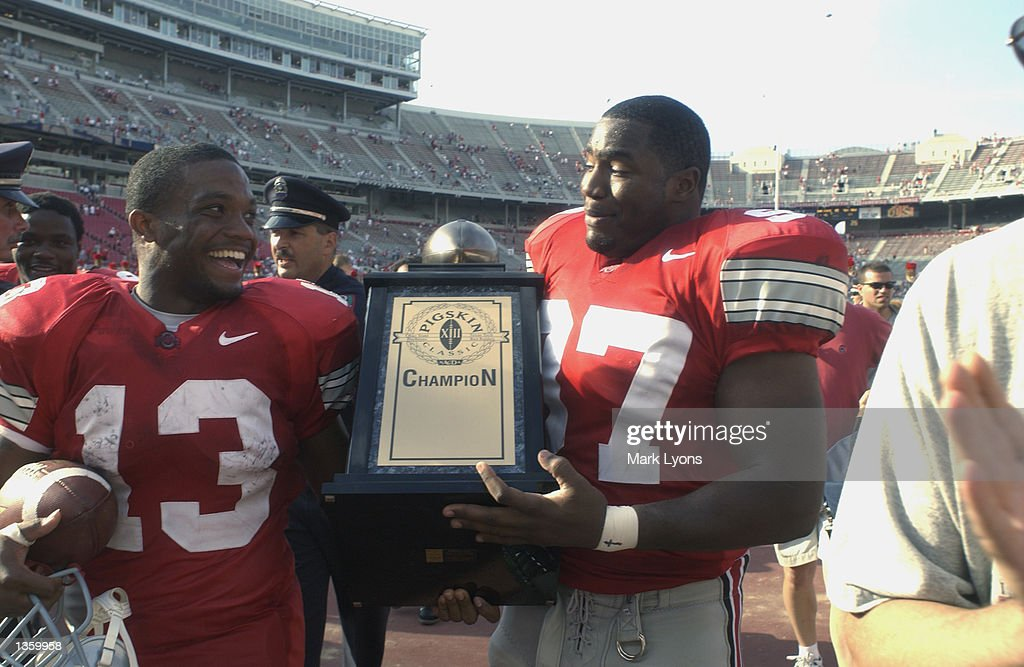 Running back Maurice Clarett #13 and defensive tackle Kenny Peterson #97 of the Ohio State Buckeyes hold the Pigskin Classic trophy after winning the NCAA Pigskin Classic against the Texas Tech Red Raiders on August 24, 2002 at Ohio Stadium in Columbus, Ohio. Ohio State defeated Texas Tech 45-21.