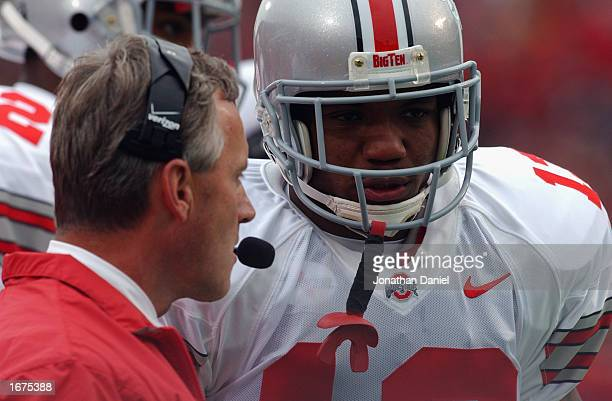 Running back Maurice Clarett of the Ohio State Buckeyes listens to head coach Jim Tressel during the Big Ten Conference football game against the...