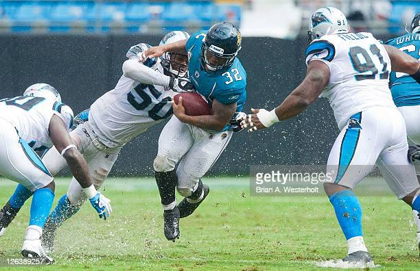 Running back Maurice JonesDrew of the Jacksonville Jaguars gets hit by linebacker James Anderson of the Carolina Panthers during third quarter action...