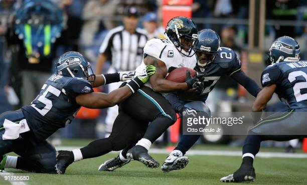 Running back Maurice Jones-Drew of the Jacksonville Jaguars rushes against Darryl Tapp and Jordan Babineaux of the Seattle Seahawks on October 11,...