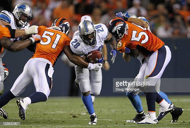 Running back Maurice Morris of the Detroit Lions rushes the ball as linebackers Akin Ayodele and Robert Ayers of the Denver Broncos defend during...