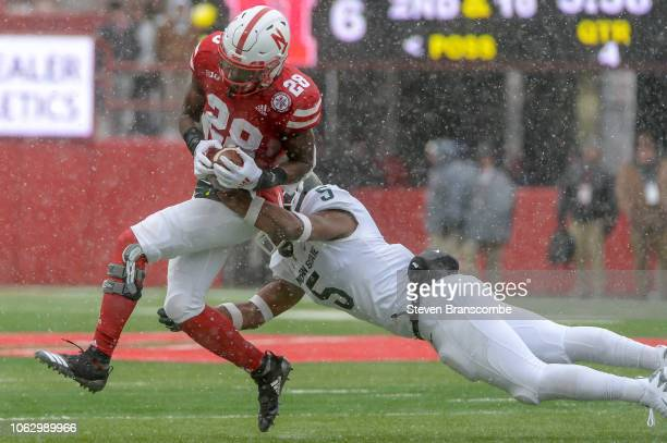 Running back Maurice Washington of the Nebraska Cornhuskers attempts to escape the tackle of linebacker Andrew Dowell of the Michigan State Spartans...