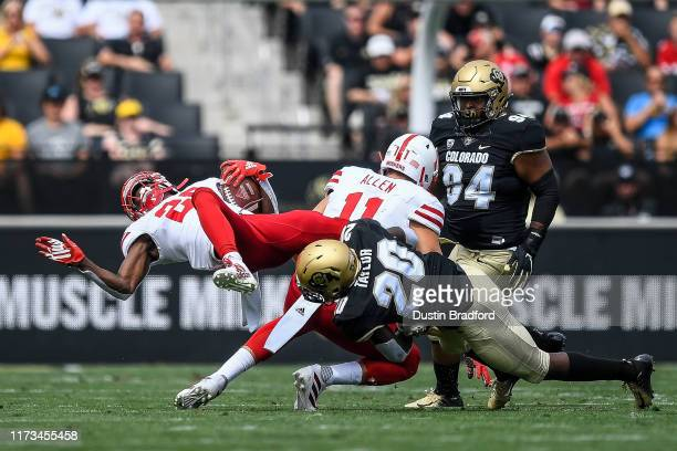 Running back Maurice Washington of the Nebraska Cornhuskers is hit by linebacker Davion Taylor of the Colorado Buffaloes in the first quarter of a...