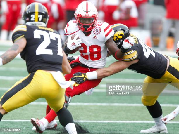 Running back Maurice Washington of the Nebraska Cornhuskers is stopped in the first half by defensive back Jack Hockaday of the Iowa Hawkeyes on...