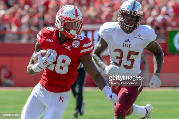Running back Maurice Washington of the Nebraska Cornhuskers runs from linebacker Tyler Murray of the Troy Trojans in the first half at Memorial...
