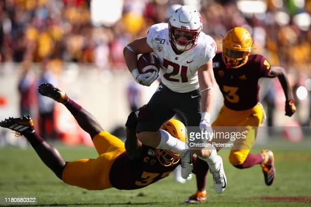 Running back Max Borghi of the Washington State Cougars rushes the football past linebacker Darien Butler of the Arizona State Sun Devils during the...