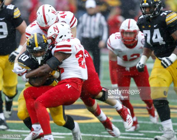 Running back Mekhi Sargent of the Iowa Hawkeyes is brought down during the second half by defensive lineman Mick Stoltenberg and safety Aaron...