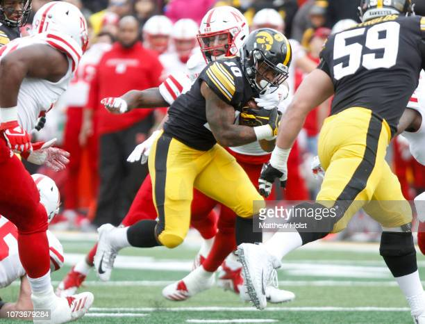 Running back Mekhi Sargent of the Iowa Hawkeyes runs up the field during the first half past linebacker Dedrick Young of the Nebraska Cornhuskers on...