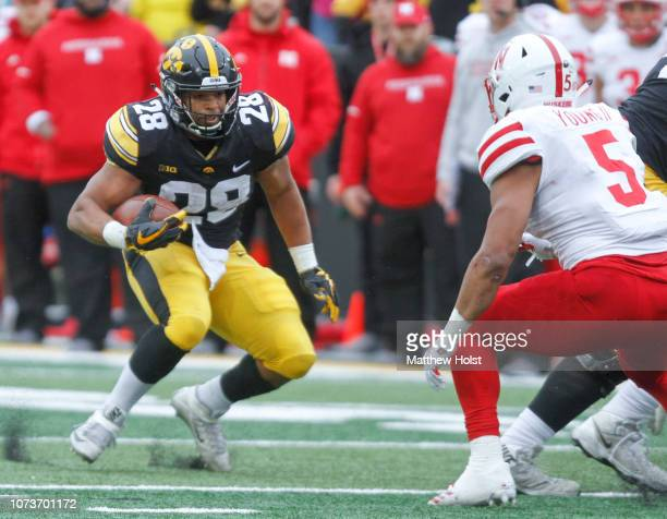 Running back Mekhi Sargent of the Iowa Hawkeyes runs up the field during the second half in front of linebacker Dedrick Young of the Nebraska...