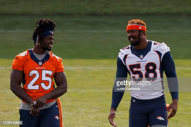 Running back Melvin Gordon and linebacker Von Miller of the Denver Broncos talk on the field during a training session at UCHealth Training Center on...