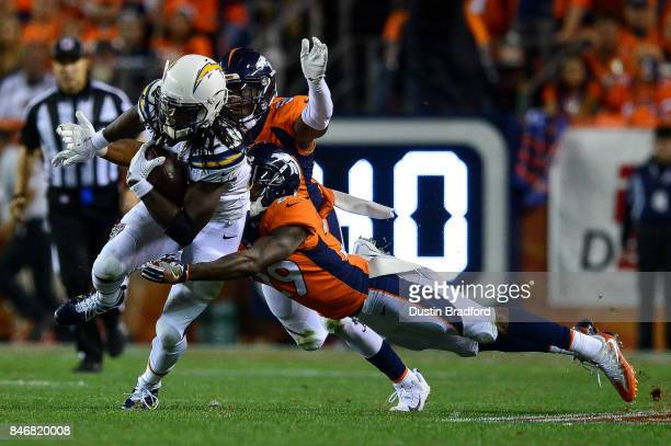 Running back Melvin Gordon of the Los Angeles Chargers is hit by cornerback Bradley Roby and inside linebacker Brandon Marshall of the Denver Broncos...
