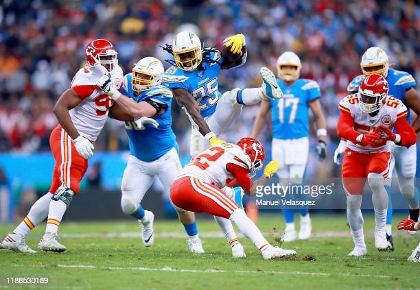 Running back Melvin Gordon of the Los Angeles Chargers leaps strong safety Tyrann Mathieu of the Kansas City Chiefs during a run in the game at...