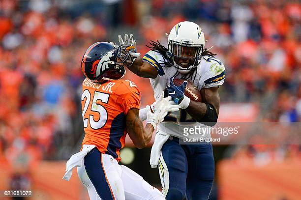 Running back Melvin Gordon of the San Diego Chargers carries the ball for 17 yards and pushes off of cornerback Chris Harris of the Denver Broncos in...