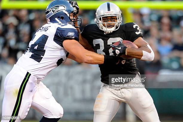 Running back Michael Bennett of the Oakland Raiders tries to break the tackle of linebacker Will Herring of the Seattle Seahawks during a preseason...