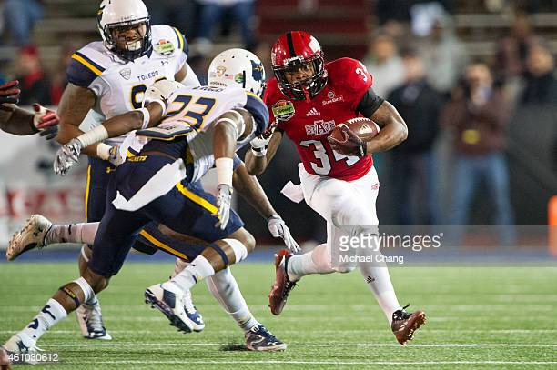 Running back Michael Gordon of the Arkansas State Red Wolves looks to maneuver by defensive back DeJuan Rogers of the Toledo Rockets during the first...
