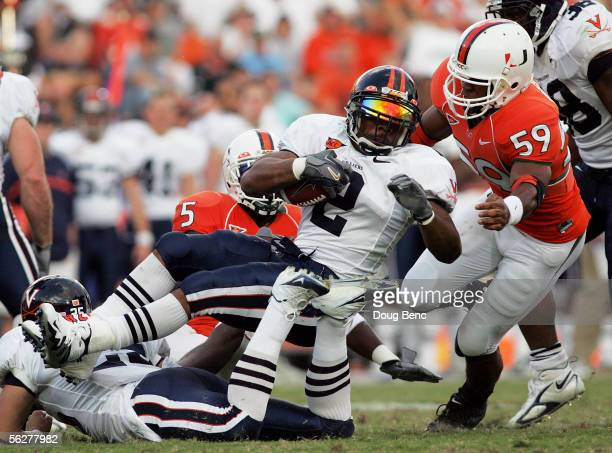 Running back Michael Johnson of the Virginia Cavaliers gets tripped up by defensive back Greg Threat and linebacker Eric Houston of the Miami...
