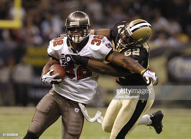 Running back Michael Pittman of the Tampa Bay Buccaneers attempts to run through the tackle by linebacker Sedrick Hodge of the New Orleans Saints...