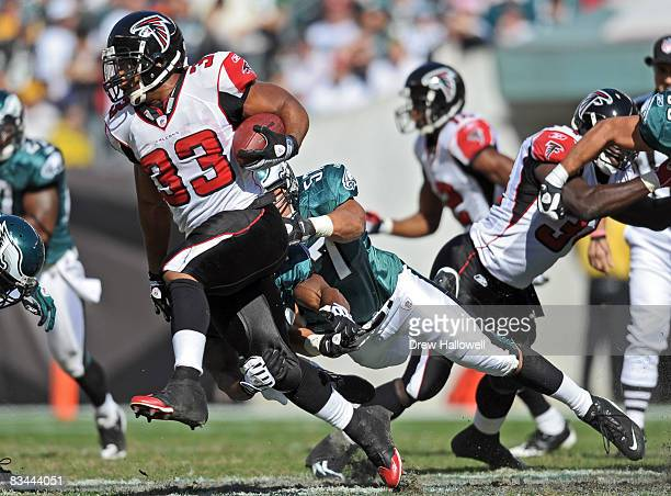 Running back Michael Turner of the Atlanta Falcons runs with the ball while getting pulled down by linebacker Chris Gocong of the Philadelphia Eagles...