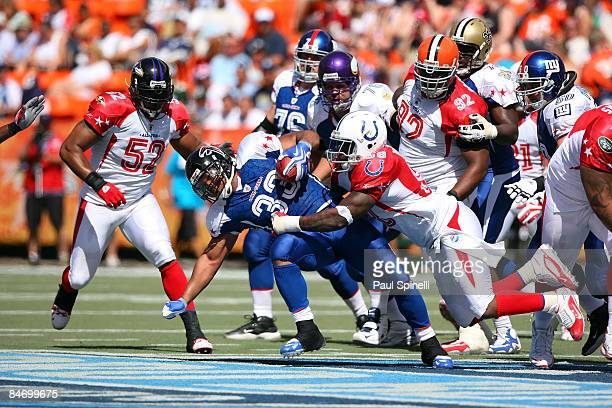 Running back Michael Turner of the NFC AllStars Atlanta Falcons gets tackled by defensive end Robert Mathis of the AFC AllStars Indianapolis Colts in...