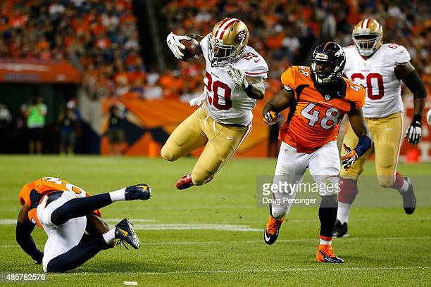 Running back Mike Davis of the San Francisco 49ers leaps to avoid the defense of strong safety David Bruton of the Denver Broncos during preseason...