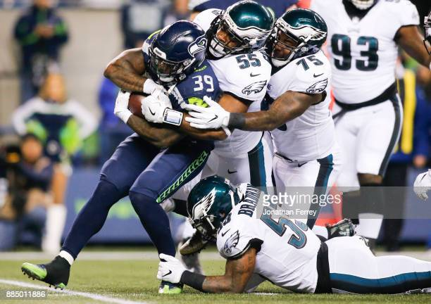 Running back Mike Davis of the Seattle Seahawks drags defensive end Brandon Graham of the Philadelphia Eagles, Vinny Curry and Nigel Bradham as he...