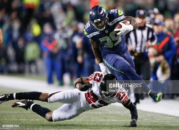 Running back Mike Davis of the Seattle Seahawks jumps over cornerback Robert Alford of the Atlanta Falcons as he rushes in the second quarter during...