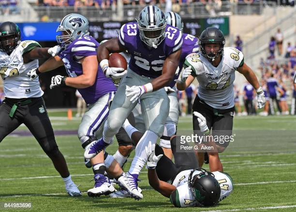 Running back Mike McCoy of the Kansas State Wildcats rushes over the top of free safety AJ McDonald of the Charlotte 49ers for a touchdown during the...