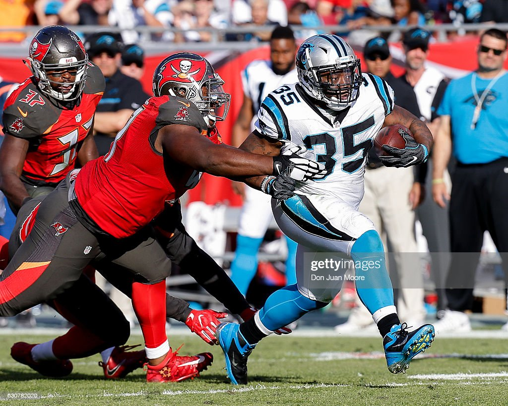 Running back Mike Tolbert #35 of the Carolina Panthers breaks a tackle from defensive tackle Akeem Spence #97 of the Tampa Bay Buccaneers during the game at Raymond James Stadium on January 1, 2017 in Tampa, Florida. The Buccaneers defeated the Panthers 17-16.