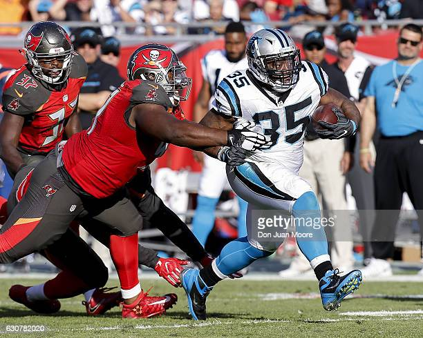 Running back Mike Tolbert of the Carolina Panthers breaks a tackle from defensive tackle Akeem Spence of the Tampa Bay Buccaneers during the game at...