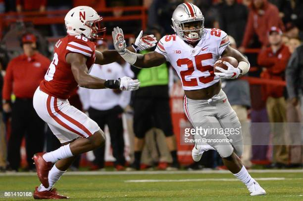 Running back Mike Weber of the Ohio State Buckeyes runs from defensive back Joshua Kalu of the Nebraska Cornhuskers at Memorial Stadium on October 14...