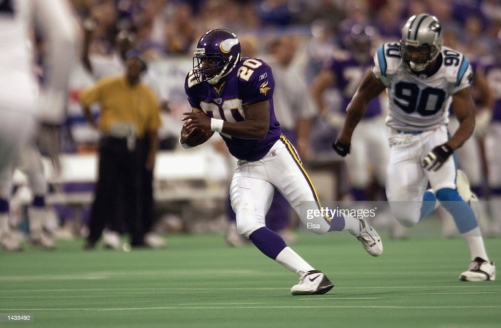 Running back Moe Williams #20 of the Minnesota Vikings carries the ball as defensive end Julius Peppers # 90 of the Carolina Panthers pursues during the game on September 22, 2002 at the Hubert H. Humphrey Metrodome in Minneapolis, Minnesota. The Panthers defeated the Vikings 21-14.