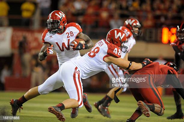 Running back Montee Ball of the Wisconsin Badgers avoids members of the Nebraska Cornhuskers defense with help from teammate tight end Jacob Pedersen...