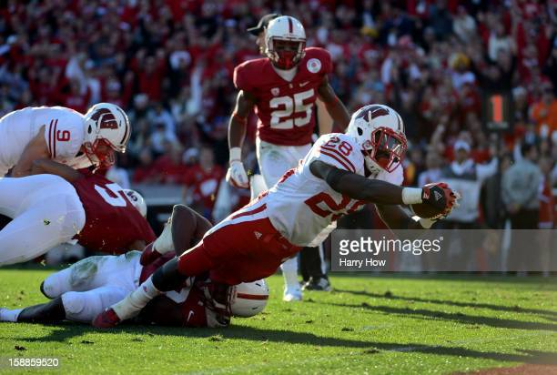 Running back Montee Ball of the Wisconsin Badgers dives to score a 10yard touchdown in the second quarter against the Stanford Cardinal in the 99th...