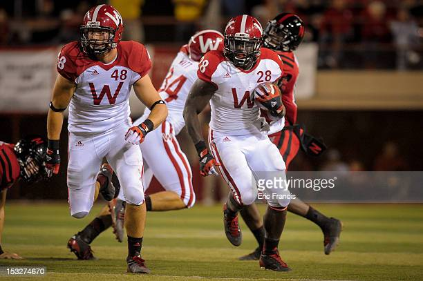 Running back Montee Ball of the Wisconsin Badgers is escorted by teammate tight end Jacob Pedersen through the Nebraska Cornhuskers at Memorial...