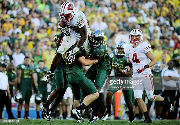 Running back Montee Ball of the Wisconsin Badgers leaps over John Boyett of the Oregon Ducks in the third quarter at the 98th Rose Bowl Game on...