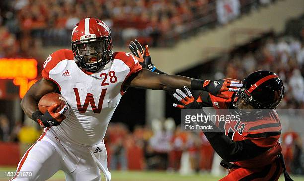Running back Montee Ball of the Wisconsin Badgers stiff arms safety PJ Smith of the Nebraska Cornhuskers during their game at Memorial Stadium on...