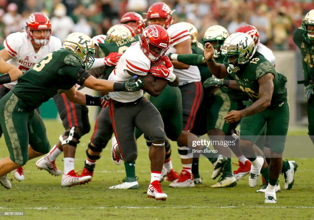 Running back Mulbah Car #34 of the Houston Cougars runs for a first down between linebacker Auggie Sanchez #43 of the South Florida Bulls and safety Tajee Fullwood #13 during the third quarter of an NCAA football game on October 28, 2017 at Raymond James Stadium in Tampa, Florida.