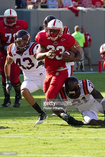 Running back Mustafa Greene of the North Carolina State Wolfpack runs with the ball from Jeron GouveiaWinslow and Rashad Carmichael of the Virginia...