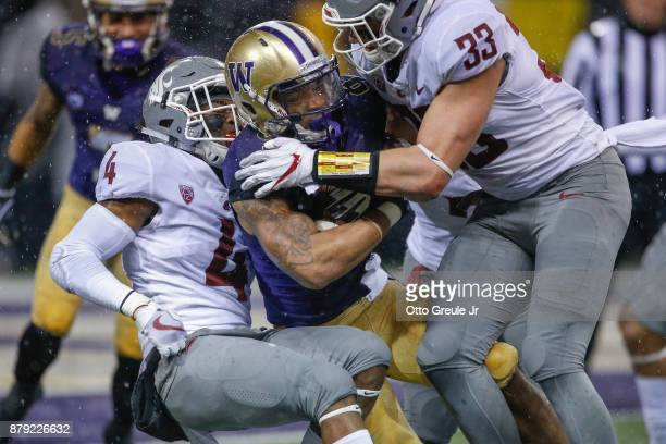 Running back Myles Gaskin of the Washington Huskies is tackled by linebacker Dylan Hanser and linebacker Tristan Brock of the Washington State...