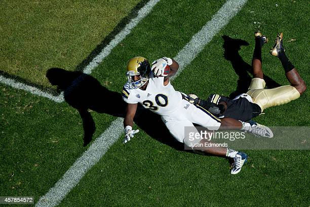 Running back Myles Jack of the UCLA Bruins reaches the football over the goal line for a touchdown as cornerback Kenneth Crawley of the Colorado...