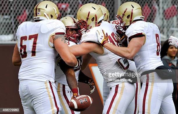 Running back Myles Willis of the Boston College Eagles is surrounded by teammates as he celebrates his touchdown run against the Virginia Tech Hokies...