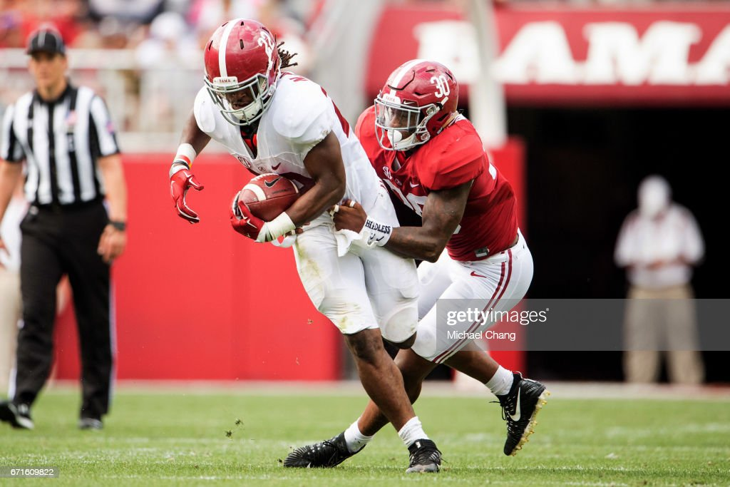Running back Najee Harris #22 of the Alabama Crimson Tide attempts to escape a tackle by linebacker Mack Wilson #30 of the Alabama Crimson Tide at Bryant-Denny Stadium on April 22, 2017 in Tuscaloosa, Alabama.